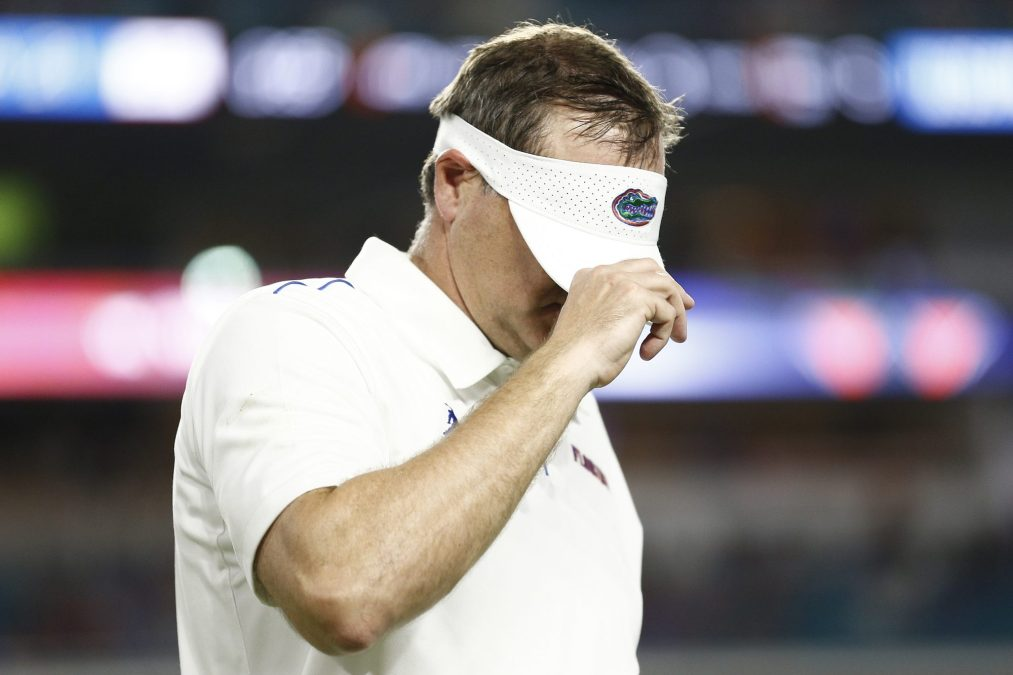 Dan Mullen, in happier times, covers his face with a visor.