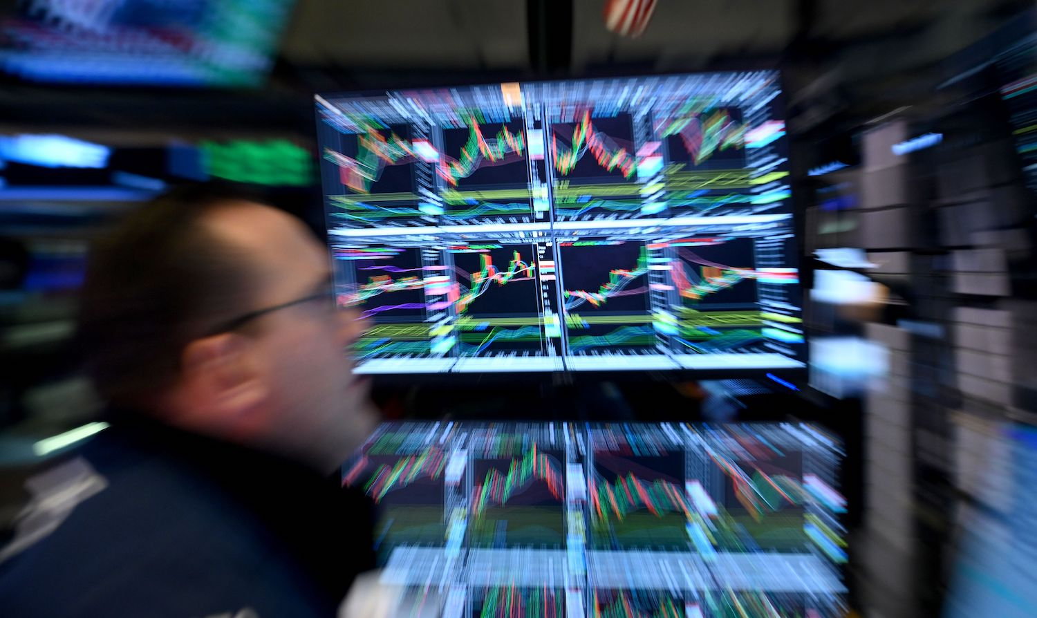 A trader walks past a screen during the closing bell at the New York Stock Exchange (NYSE) on March 17, 2020 at Wall Street in New York City. - Wall Street stocks rallied Tuesday on expectations for massive federal stimulus to address the economic hit from the coronavirus, partially recovering some of their losses from the prior session. (Photo by Johannes EISELE / AFP) (Photo by JOHANNES EISELE/AFP via Getty Images)