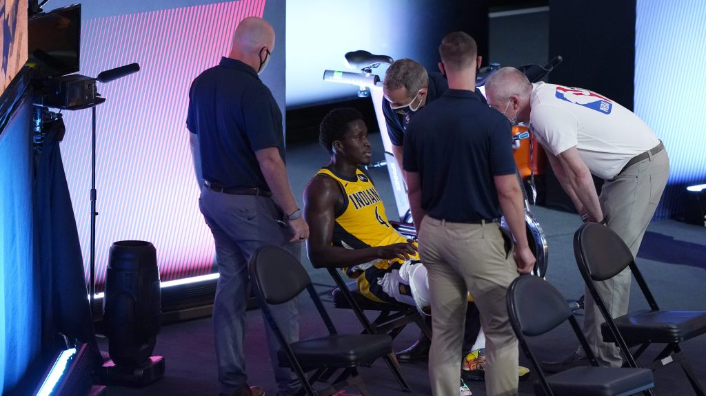 Victor Oladipo of the Indiana Pacers, surrounded by team staffers