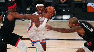 Shai Gilgeous-Alexander drives toward the basket between Houston Rockets defenders