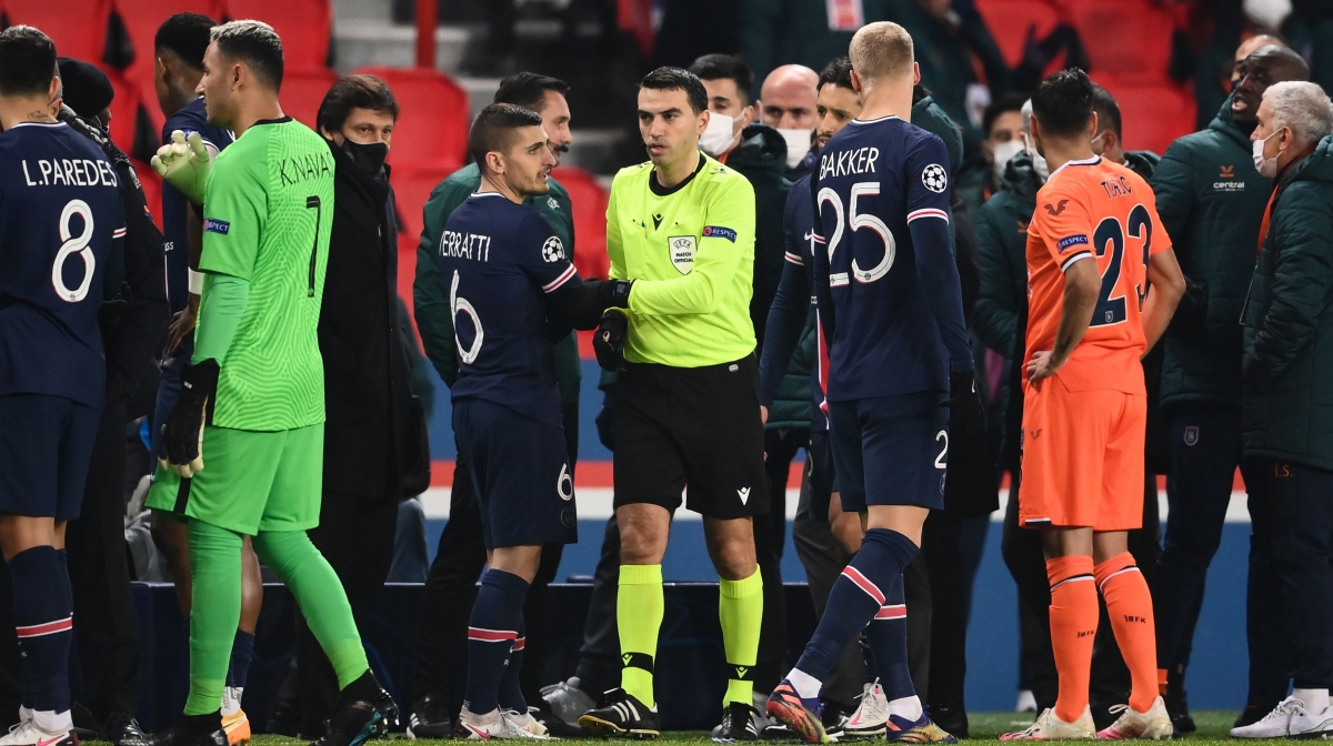 Romanian referee Ovidiu Hategan (in yellow) passes by Paris Saint-Germain's Italian midfielder Marco Verratti (CL) after the game was suspended amid allegations of racism by one of the match officials during the UEFA Champions League group H football match between Paris Saint-Germain (PSG) and Istanbul Basaksehir FK