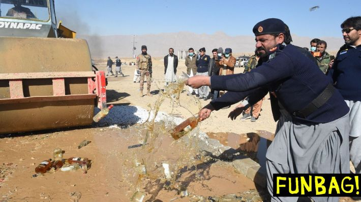Custom official destroys seized bottles of liquor, previously smuggled into Pakistan during an ceremonyorganized by customs to destroy seized alcohol and drugs smuggled into Pakistan,on the outskirts of Quetta on December 15, 2020. (Photo by Banaras KHAN / AFP) (Photo by BANARAS KHAN/AFP via Getty Images)