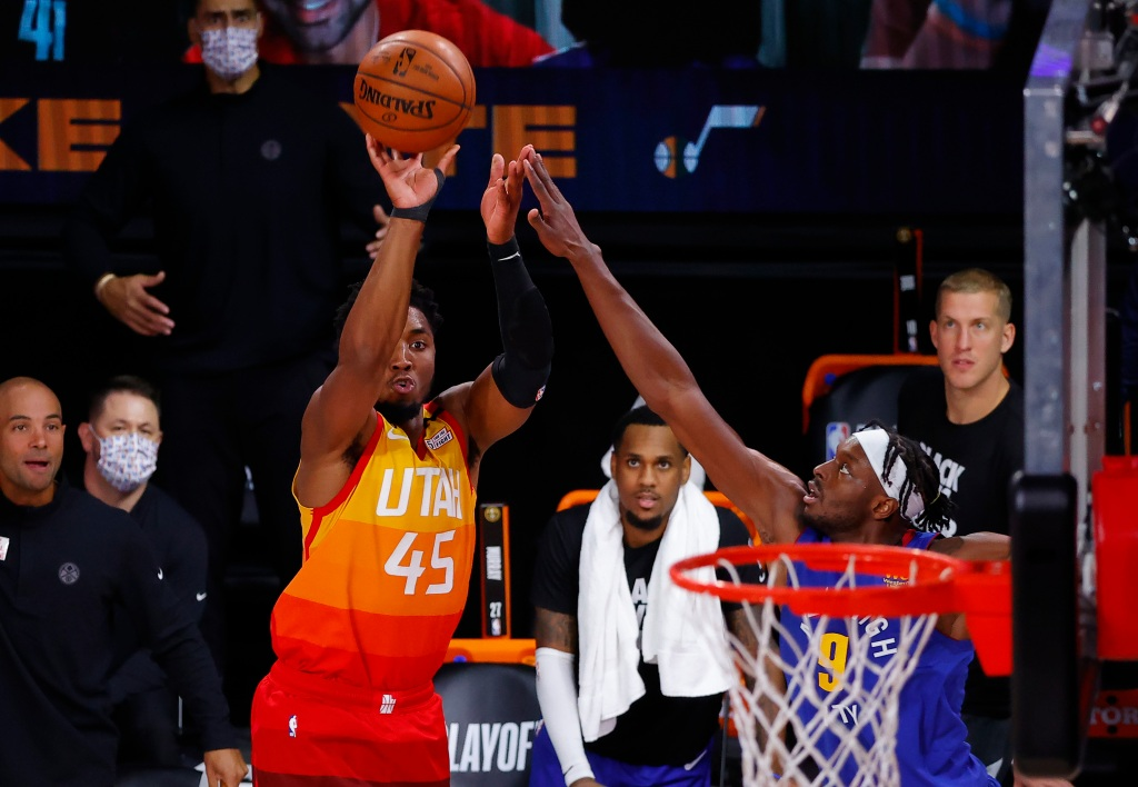 Donovan Mitchell of the Utah Jazz shoots over the outstretched arm of Jerami Grant of the Denver Nuggets