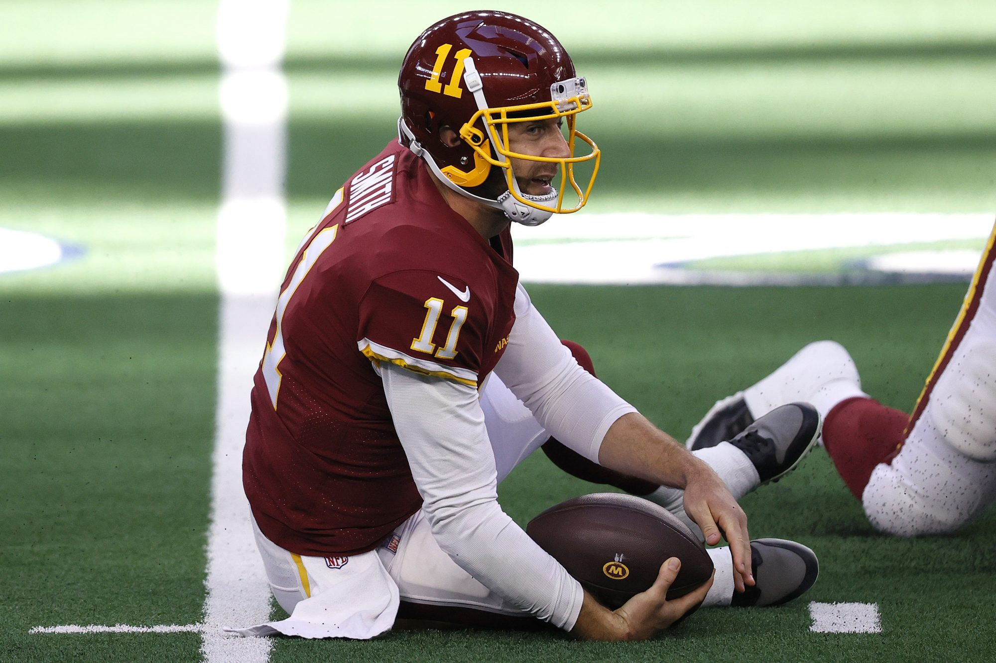 Washington Football Team quarterback Alex Smith lies crumpled on the turf after being tackled. He's fine! Both legs are intact.