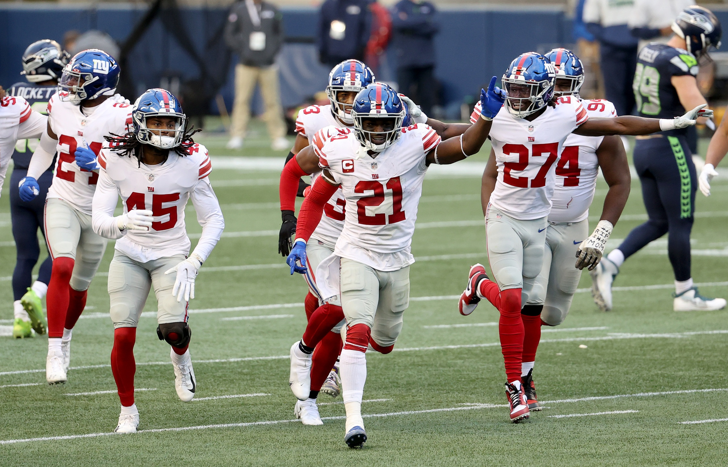 Madre Harper #45, Jabrill Peppers #21 and Isaac Yiadom #27 of the New York Giants celebrate an interception