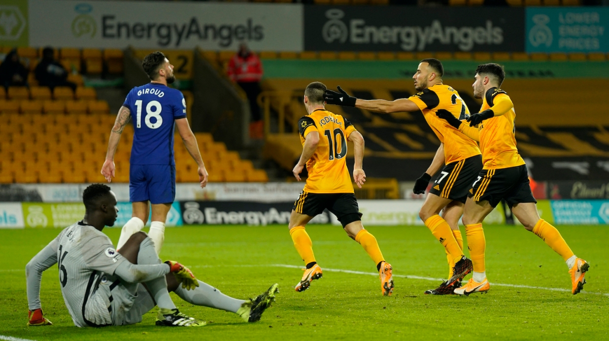 Daniel Podence of Wolverhampton Wanderers celebrates with teammates Romain Saiss and Pedro Neto after scoring their team's first goal during the Premier League match between Wolverhampton Wanderers and Chelsea at Molineux on December 15, 2020 in Wolverhampton, England. The match will be played without fans, behind closed doors as a Covid-19 precaution.