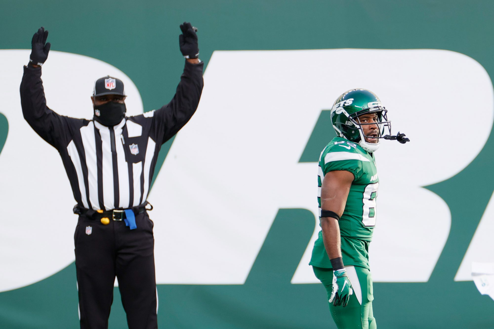 """A referee signals """"touchdown"""" behind a Jets player whose conflicted expression is inscrutable."""