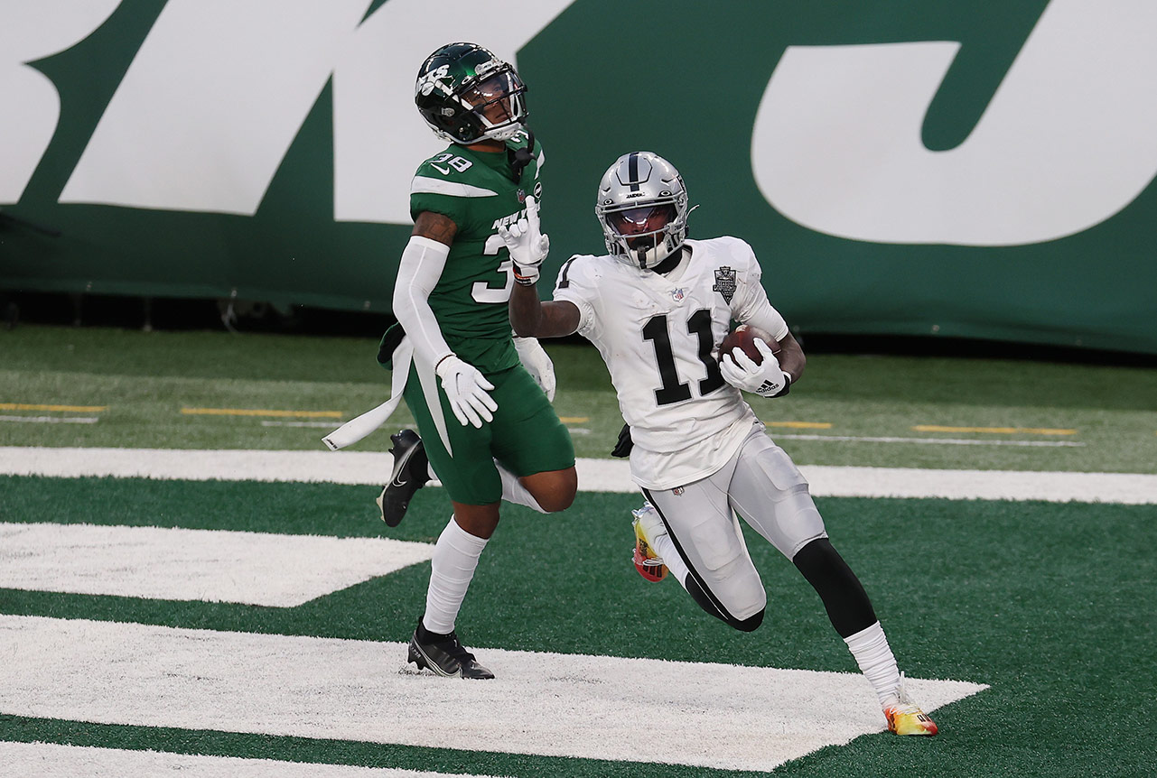 No. 11 on the Raiders celebrates in the end zone as a Jets player sighs behind him