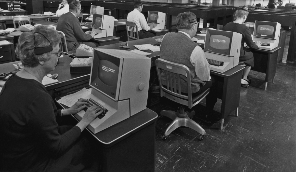 A group of office workers using telephone headsets and computers circa 1965 (Photo by Authenticated News/Archive Photos/Getty Images)