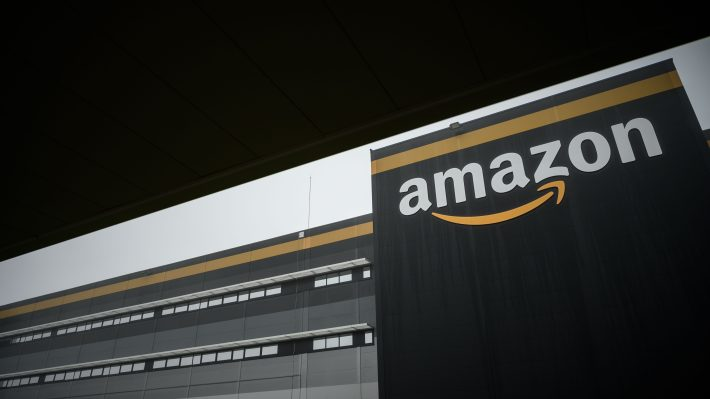 The Amazon logo at a new Amazon warehouse, set against a black sky.