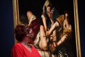 A gallery assistant poses a painting titled 'Judith beheading Holofernes' by Italian Baroque artist Artemisia Gentileschi during a photocall to preview the new Artemisia exhibition at the National Gallery in London on September 29, 2020.