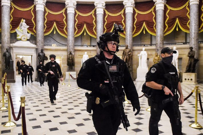 Members of the Swat team patrol and secure the Statuary Hall