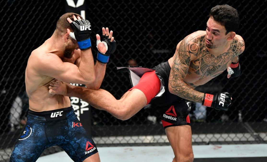 ABU DHABI, UNITED ARAB EMIRATES - JANUARY 17: In this handout image provided by UFC, Max Holloway (R) kicks Calvin Kattar in a featherweight bout during the UFC Fight Night event at Etihad Arena on UFC Fight Island on January 17, 2021 in Abu Dhabi, United Arab Emirates. (Photo by Jeff Bottari/Zuffa LLC via Getty Images)