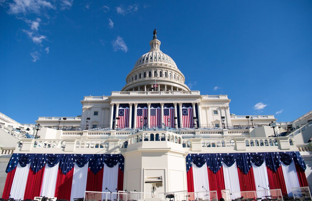 the US capitol shot from low near the ground and decorated with american flags