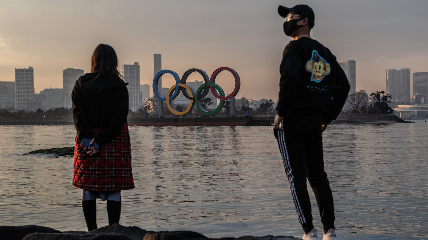 TOKYO, JAPAN - JANUARY 22: A woman and a man wearing a face mask view the Olympic Rings on January 22, 2021 in Tokyo, Japan. With just six months to go until the start of the Games, it has been reported that the Japanese authorities have privately concluded that the Olympics could not proceed due to the ongoing Covid-19 coronavirus pandemic. Spokesmen from the IOC and Japanese government have since rejected the report. (Photo by Carl Court/Getty Images)