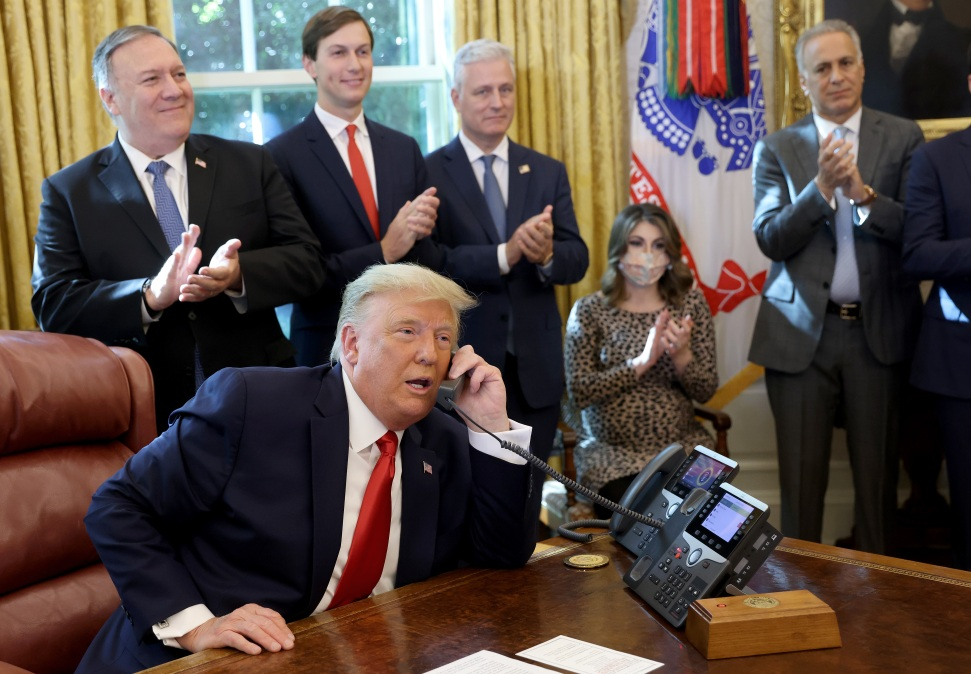 Donald Trump on the phone being applauded by lackeys, presumably not for farting.
