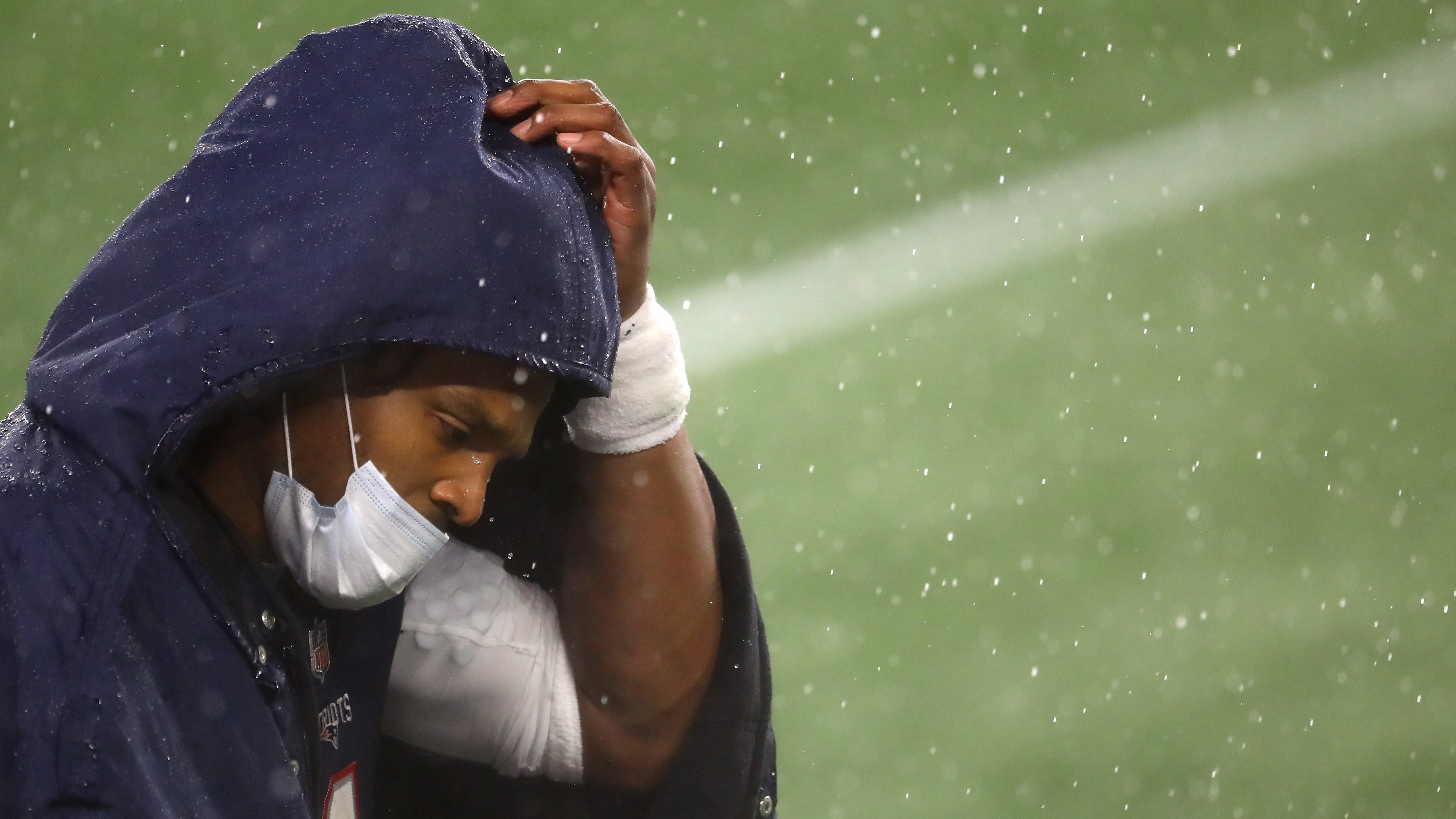Cam Newton, quarterback, of the New England Patriots, looks on from the sideline wearing a mask and rain jacket during the game against the Baltimore Ravens at Gillette Stadium on November 15, 2020 in Foxborough, Massachusetts.