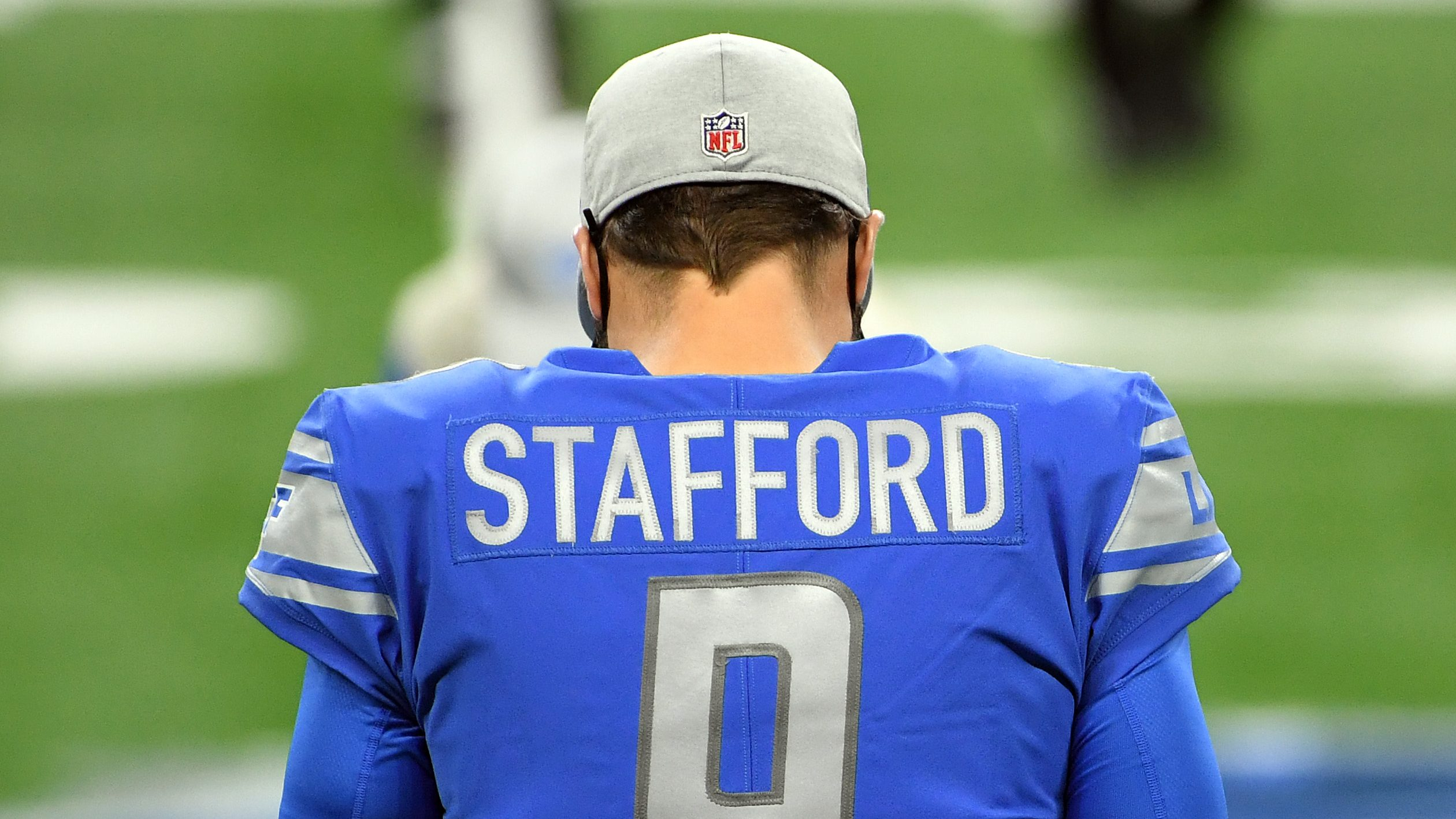 Matthew Stafford, quarterback of the Detroit Lions, stands on the field before the game against the Green Bay Packers at Ford Field on December 13, 2020 in Detroit, Michigan. Stafford has his back to the camera, all that's visible is his hat and his jersey.