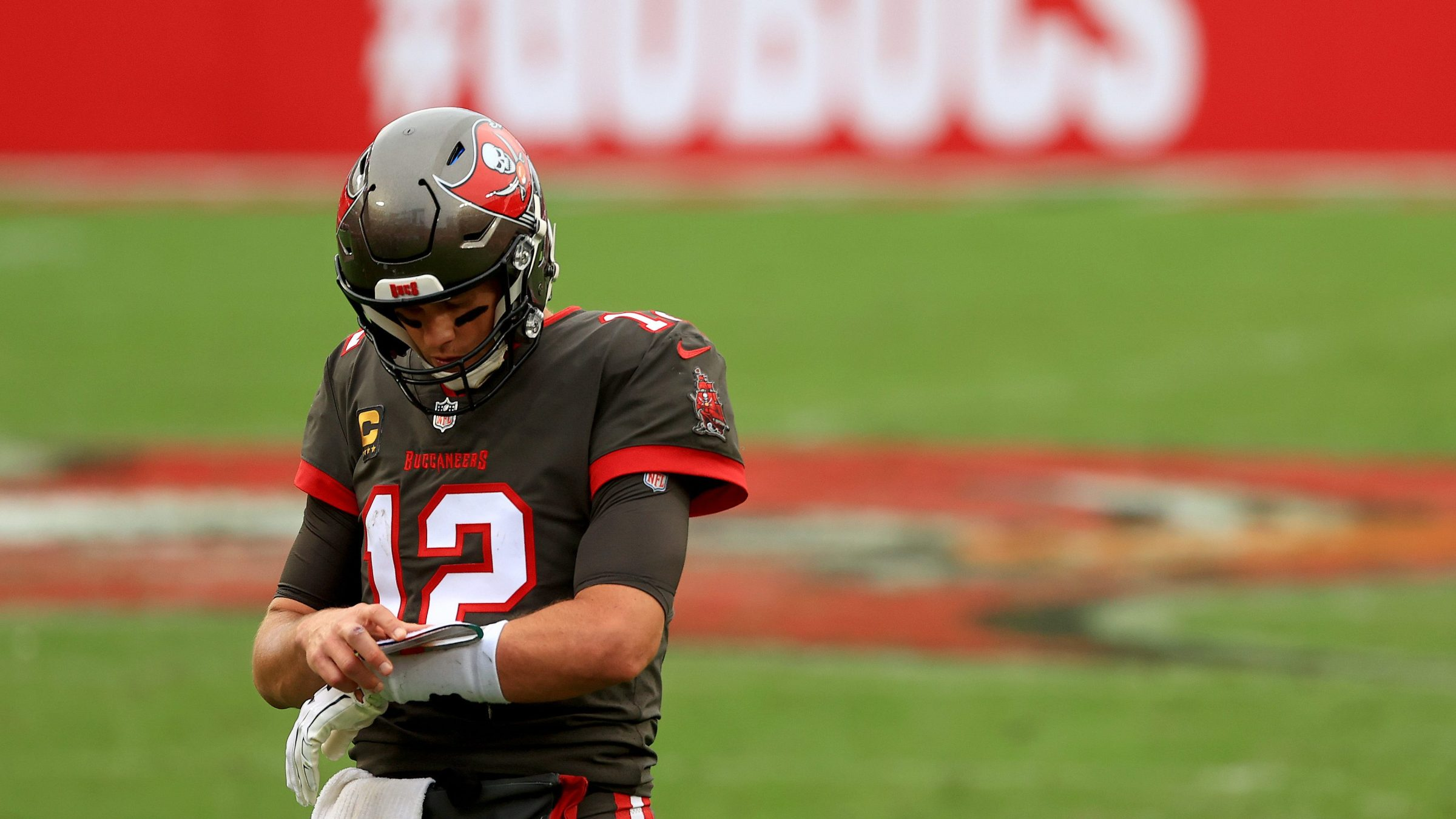 Quarterback Tom Brady looks down at his wristband during a Tampa Bay Buccaneers game.