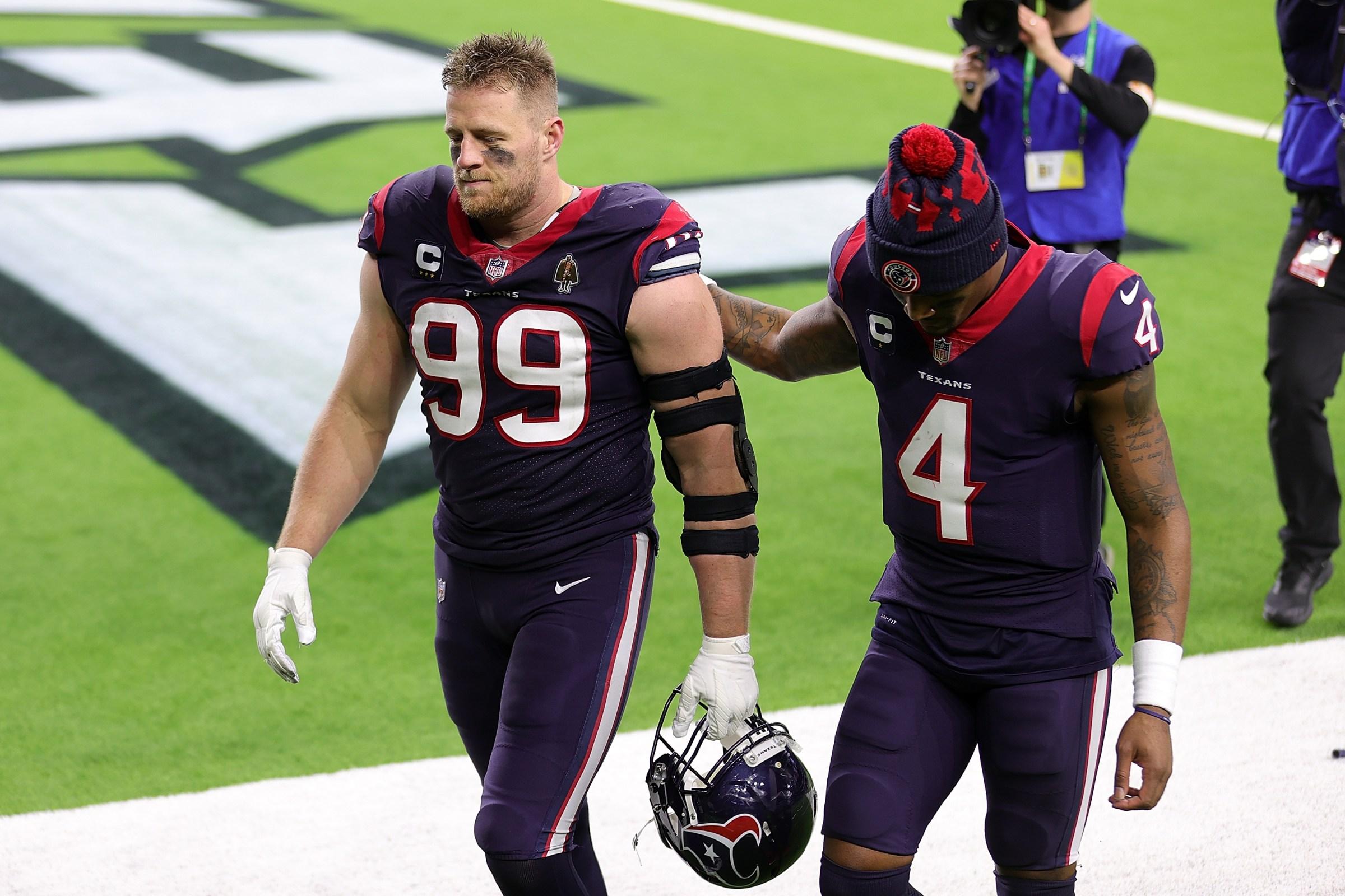 J.J. Watt #99 of the Houston Texans walks off the field with Deshaun Watson