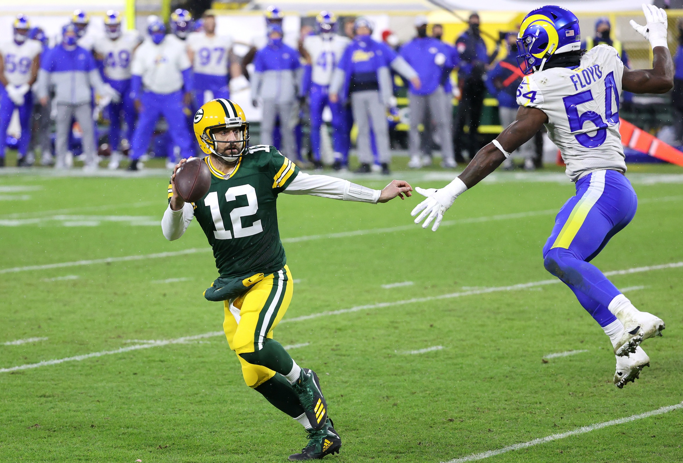 Aaron Rodgers #12 of the Green Bay Packers runs against Leonard Floyd #54 of the Los Angeles Rams for a 1-yard touchdown in the second quarter during the NFC Divisional Playoff game at Lambeau Field on January 16, 2021 in Green Bay, Wisconsin.