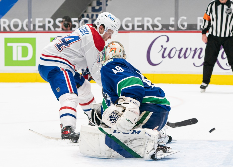 Nick Suzuki #14 of the Montreal Canadiens puts the puck past goalie Braden Holtby