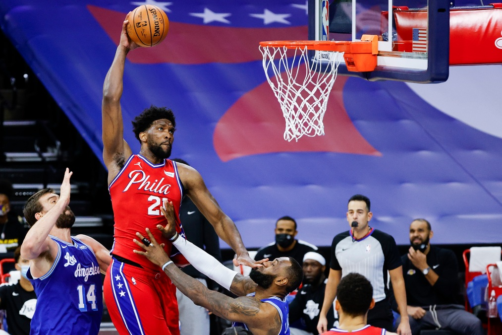 Joel Embiid #21 of the Philadelphia 76ers drives to the basket over LeBron James