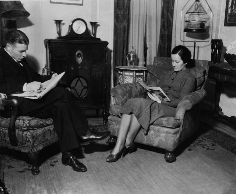 a man and a woman sit in a cozy living room and read