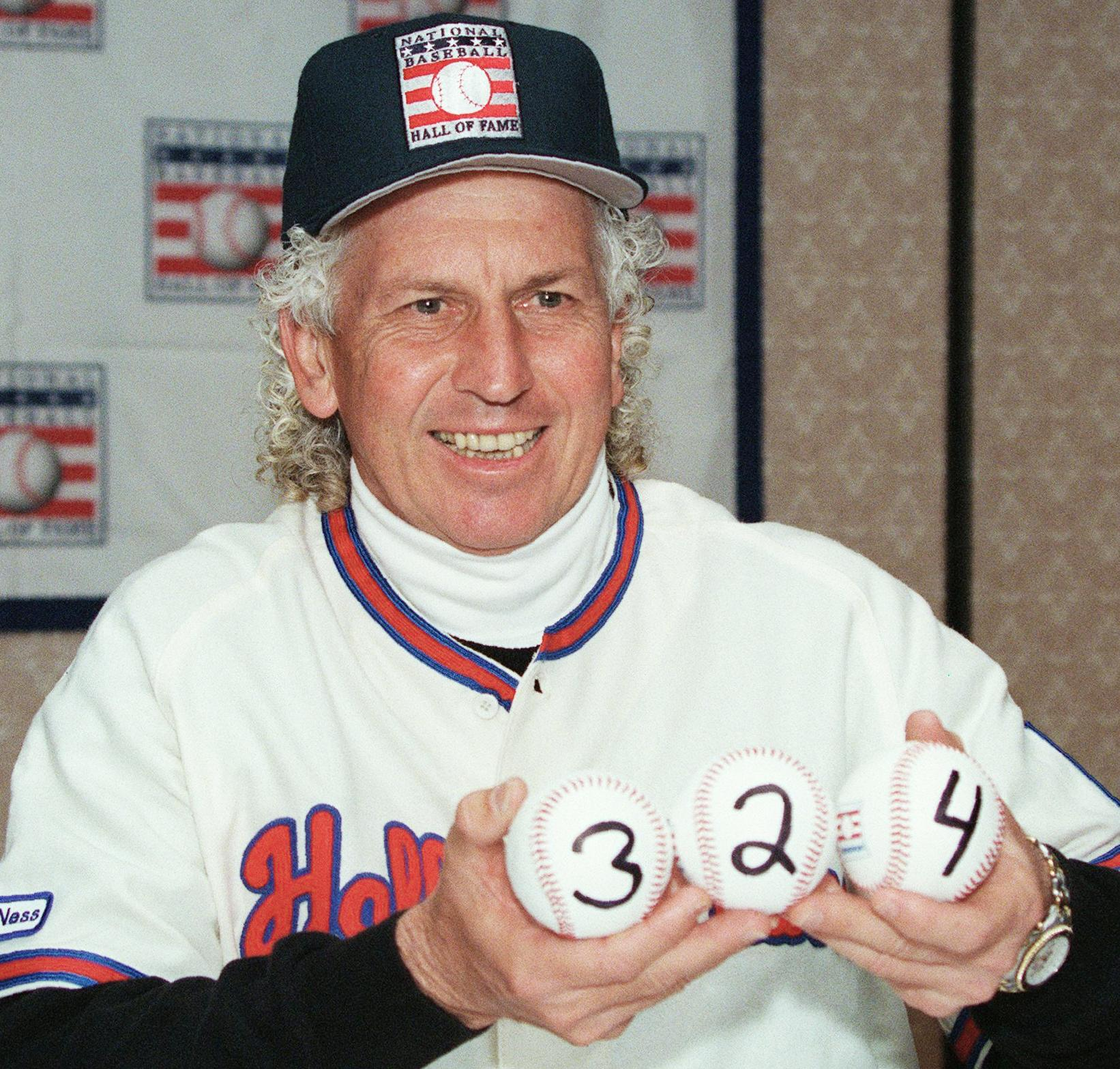 The late Don Sutton holding three baseballs marked to reflect the 324 games he won during his Hall of Fame career.
