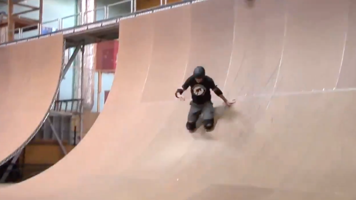 tony hawk slides on his knee pads down the side of a half pipe