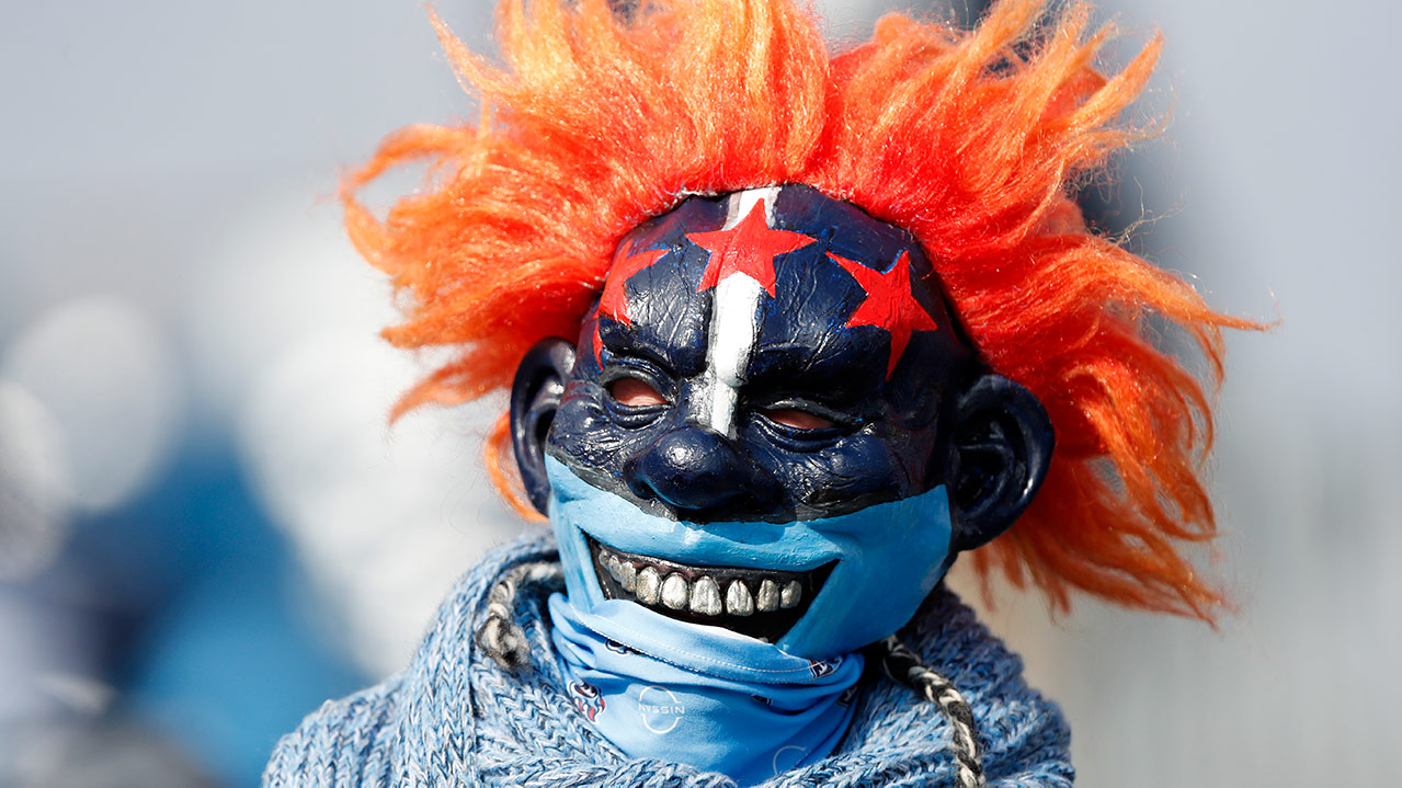 A Tennessee Titans fan wearing a blue mask with the three stars of the Nashville flag on it. He also has wild orange clown hair, and a bandana around his mouth/neck area.