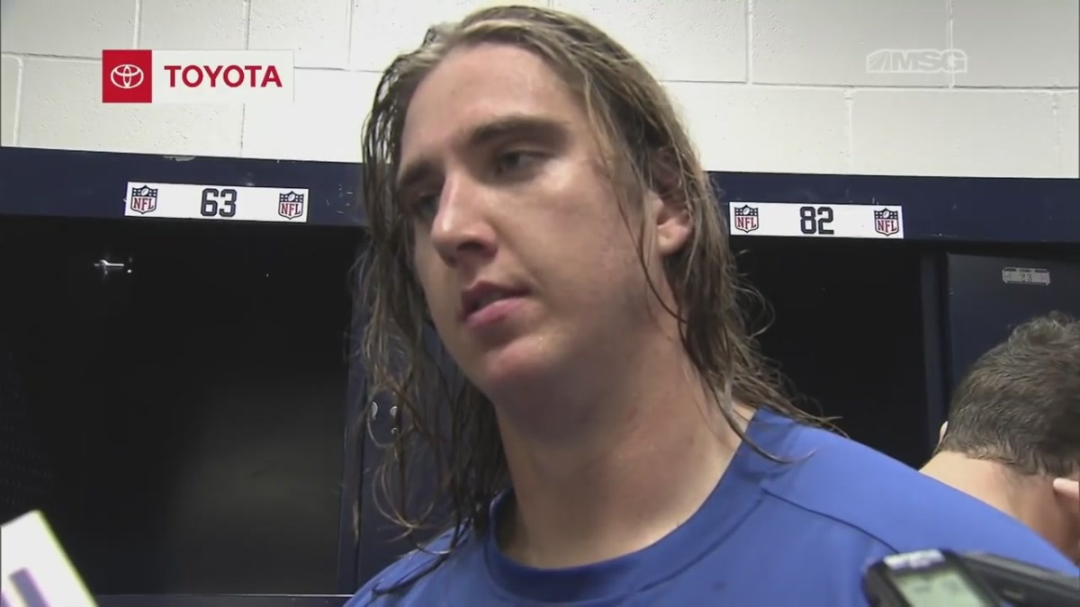 An image of football player Chad Wheeler as he is talking to reporters and standing in front of his locker.