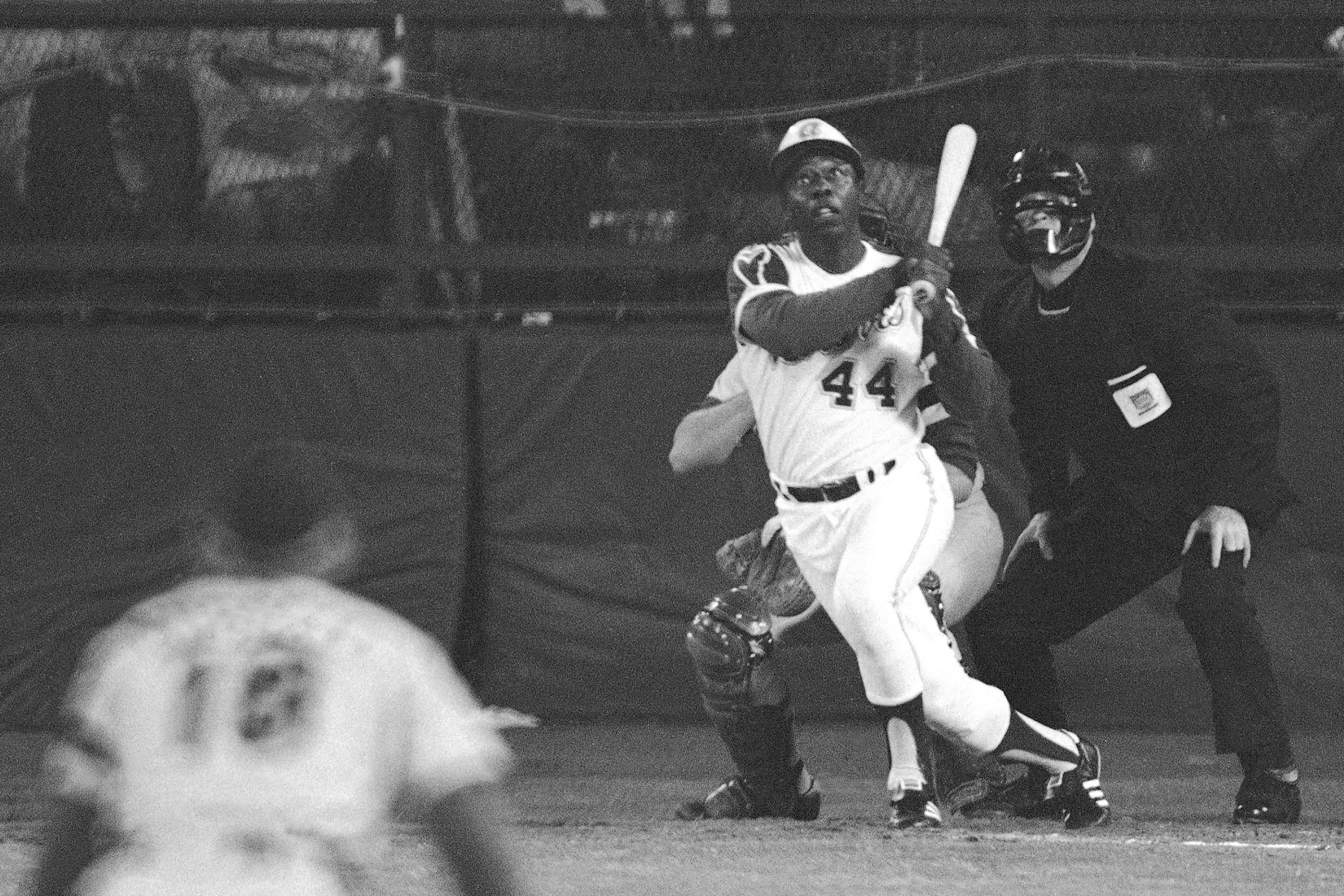 FILE - Atlanta Braves' Hank Aaron eyes the flight of the ball after hitting his 715th career homer in a game against the Los Angeles Dodgers in Atlanta, Ga., in this April 8, 1974 file photo. Dodgers pitcher Al Downing, catcher Joe Ferguson and umpire David Davidson look on. Hank Aaron, who endured racist threats with stoic dignity during his pursuit of Babe Ruth but went on to break the career home run record in the pre-steroids era, died early Friday, Jan. 22, 2021. He was 86. The Atlanta Braves said Aaron died peacefully in his sleep. No cause of death was given. (AP Photo/Harry Harrris, FIle)