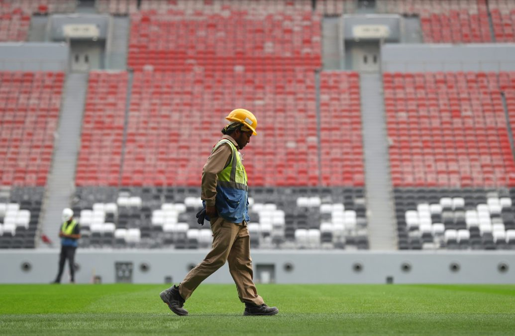A laborer walks on the field in one of the new stadiums Qatar has constructed for the 2022 World Cup.
