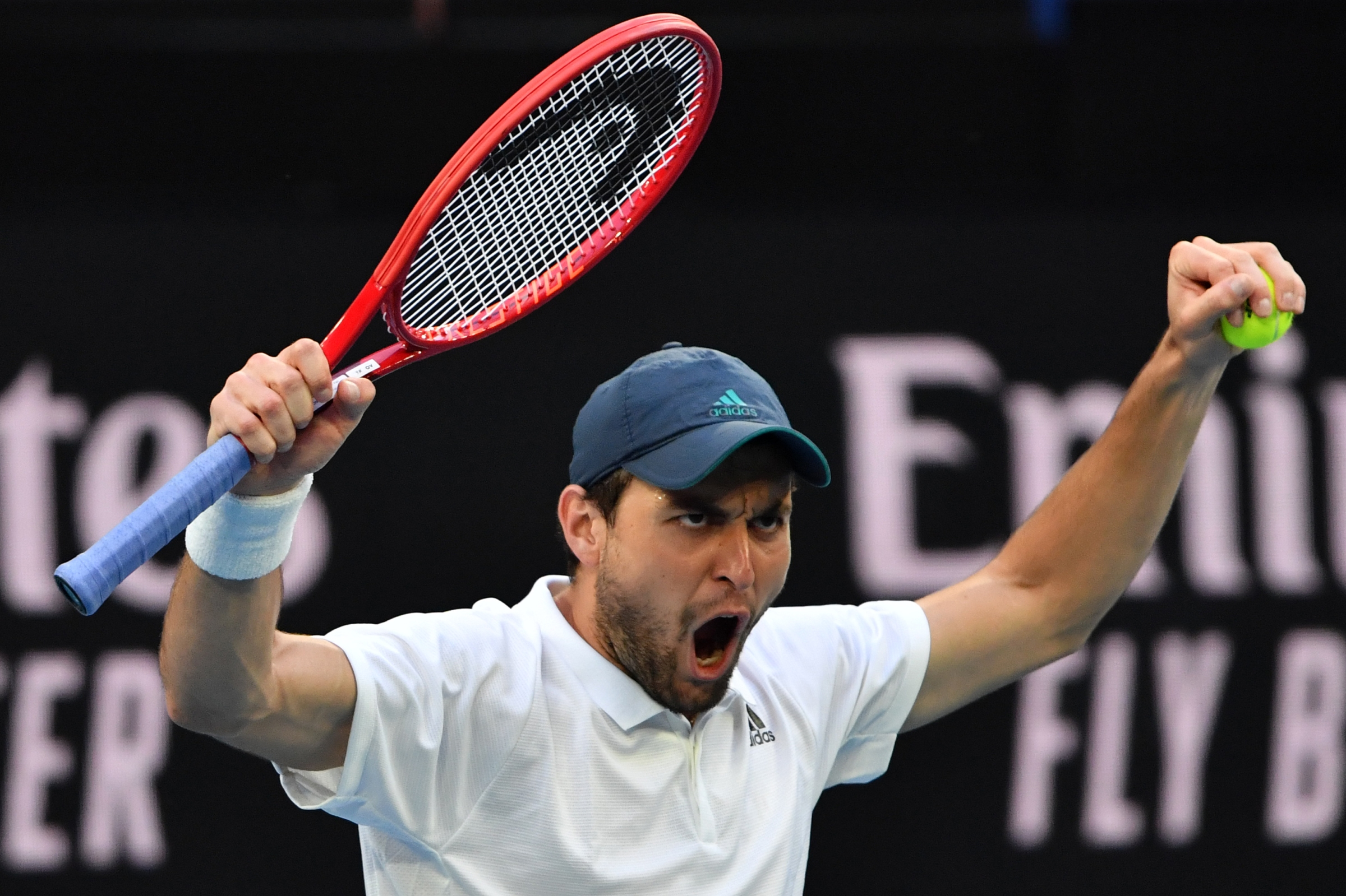 Russia's Aslan Karatsev celebrates after victory against Argentina's Diego Schwartzman during their men's singles match on day five of the Australian Open tennis tournament in Melbourne on February 12, 2021.