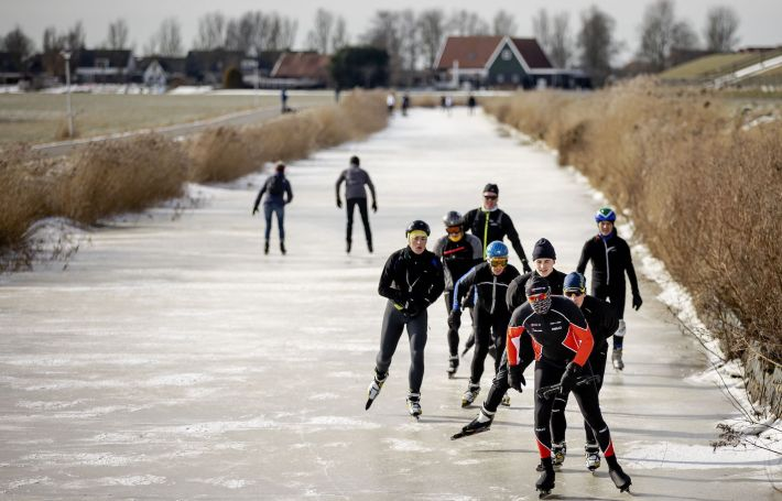 Dutch skater Henk Angenent (C/red/black) is followed by others as he glides across ice on a canal at Hindeloopen on February 14, 2021, as he attempts the 'Elfstedentocht' in the Netherlands' province of Friesland. - Angenent a farmer, who was winner of the last edition of the 'Elfstedentocht' in 1997, which is an organised 200-kilometre skating tour along the 11 Frisian towns and has been adapted to comly with restrictions as part of the ongoing coronavirus (Covid-19) pandemic. (Photo by ROBIN VAN LONKHUIJSEN / ANP / AFP) / Netherlands OUT (Photo by ROBIN VAN LONKHUIJSEN/ANP/AFP via Getty Images)