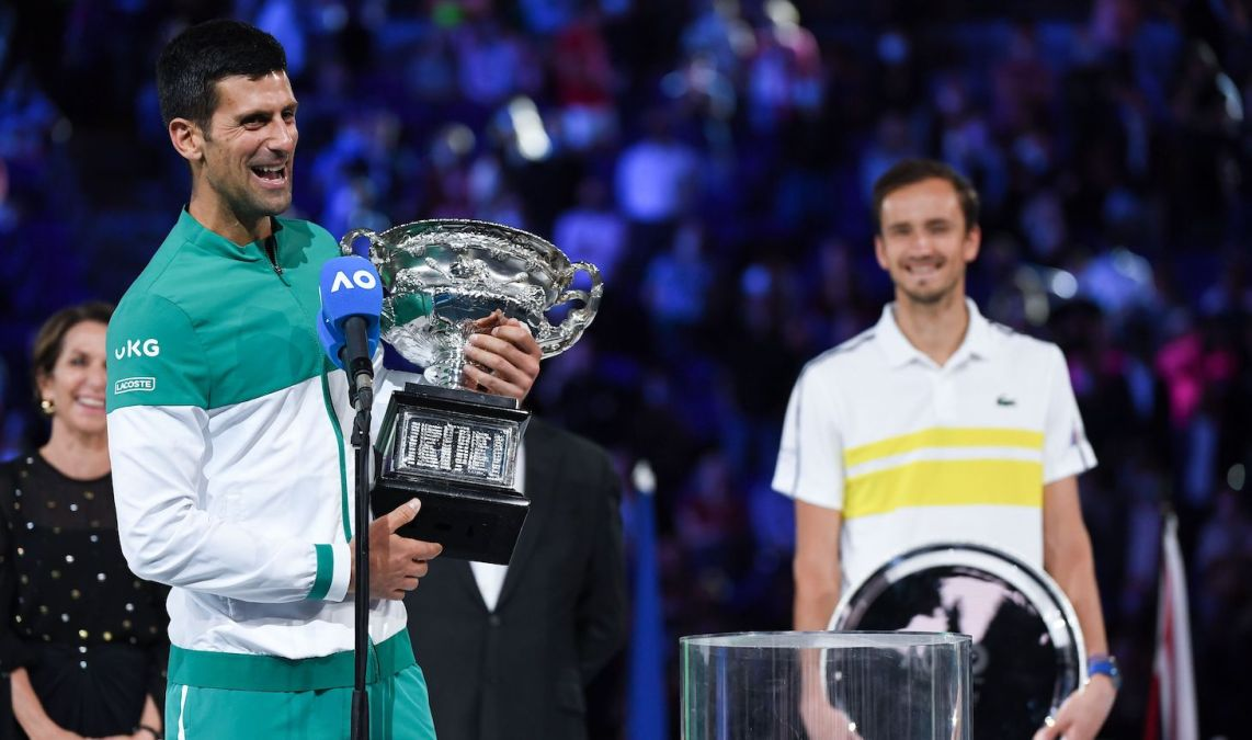 Serbia's Novak Djokovic speaks holding the Norman Brookes Challenge Cup trophy following his victory against Russia's Daniil Medvedev in their men's singles final match on day fourteen of the Australian Open tennis tournament in Melbourne on February 21, 2021. (Photo by William WEST / AFP) / -- IMAGE RESTRICTED TO EDITORIAL USE - STRICTLY NO COMMERCIAL USE -- (Photo by WILLIAM WEST/AFP via Getty Images)