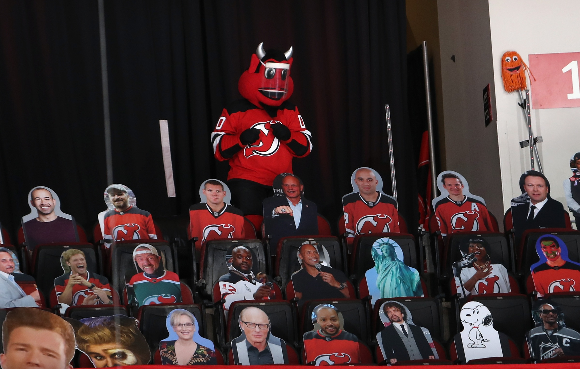 The New Jersey Devil stands in the last row of the arena surrounded by cardboard cut-outs