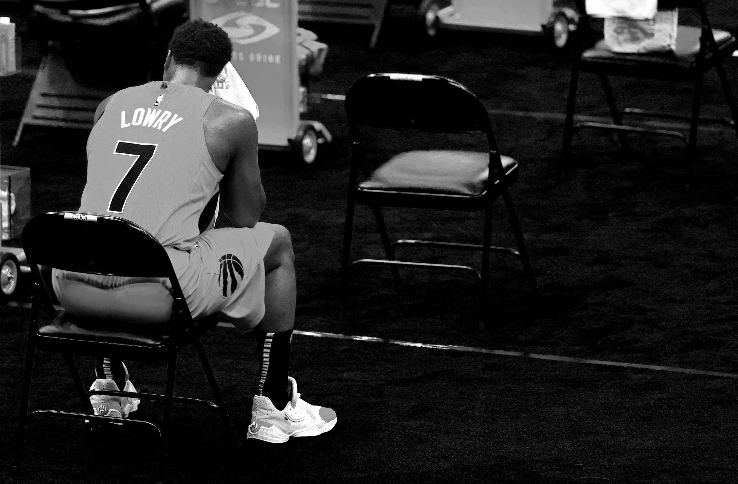 Kyle Lowry sits on the bench in a moody black-and-white image.