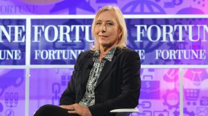 Tennis player Martina Navratilova sits onstage at the FORTUNE Most Powerful Women Summit on October 16, 2013 in Washington, DC. She wears a black jacket and a collard shirt with a purple background behind her.
