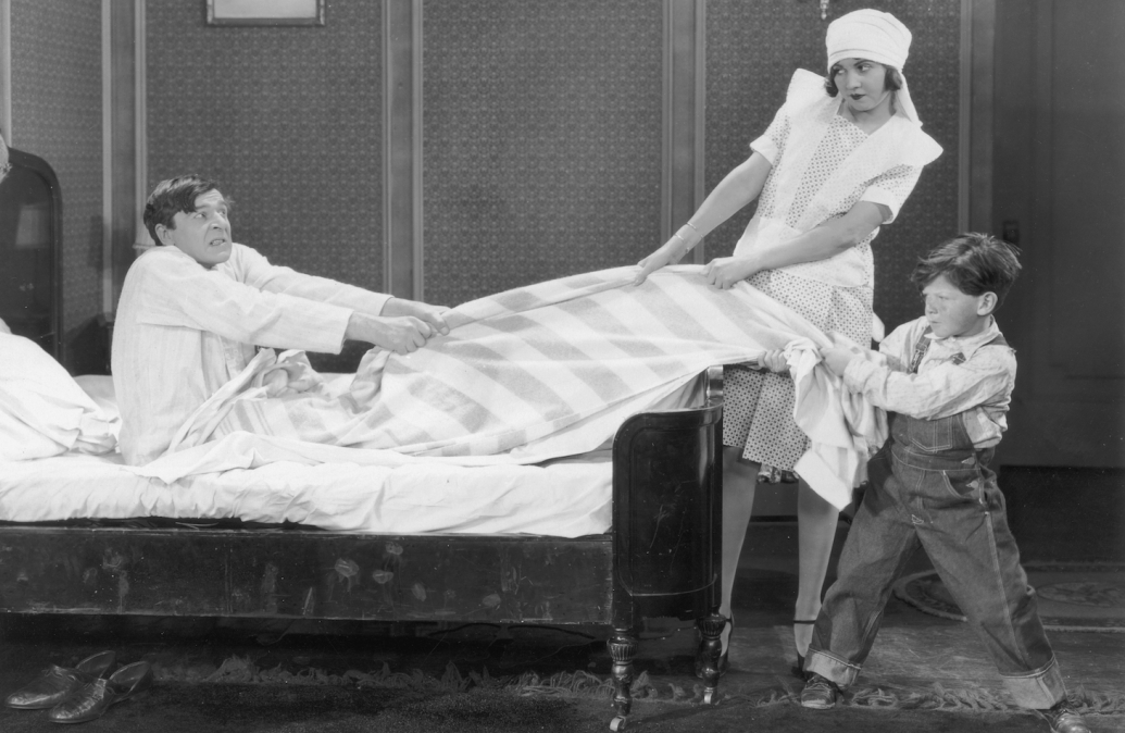 Actors Lucille Hutton and Jackie Levine play tug-of-war with Jack Miller's blanket while attempting to get him out of bed in a still from the silent film comedy 'Oh, Mama'. (Photo by Hulton Archive/Getty Images)