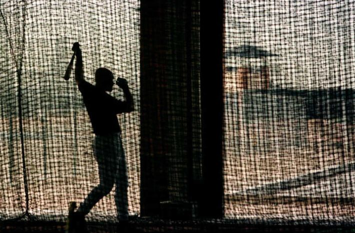 A baseball player is silhouetted as he follows through while practicing in the batting cages