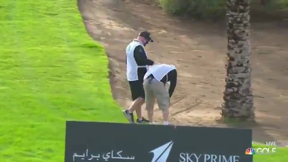 A volunteer at the Saudi International standing but bent over after being hit with a Dustin Johnson drive