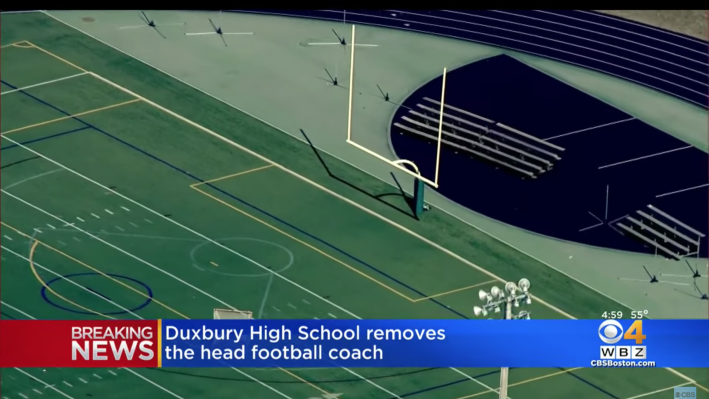 """The football field at Duxbury High School. You can see the field, a track around it, and the goal posts. There's also a TV graphic that says """"Breaking News: Duxbury High School removes the head football coach."""""""