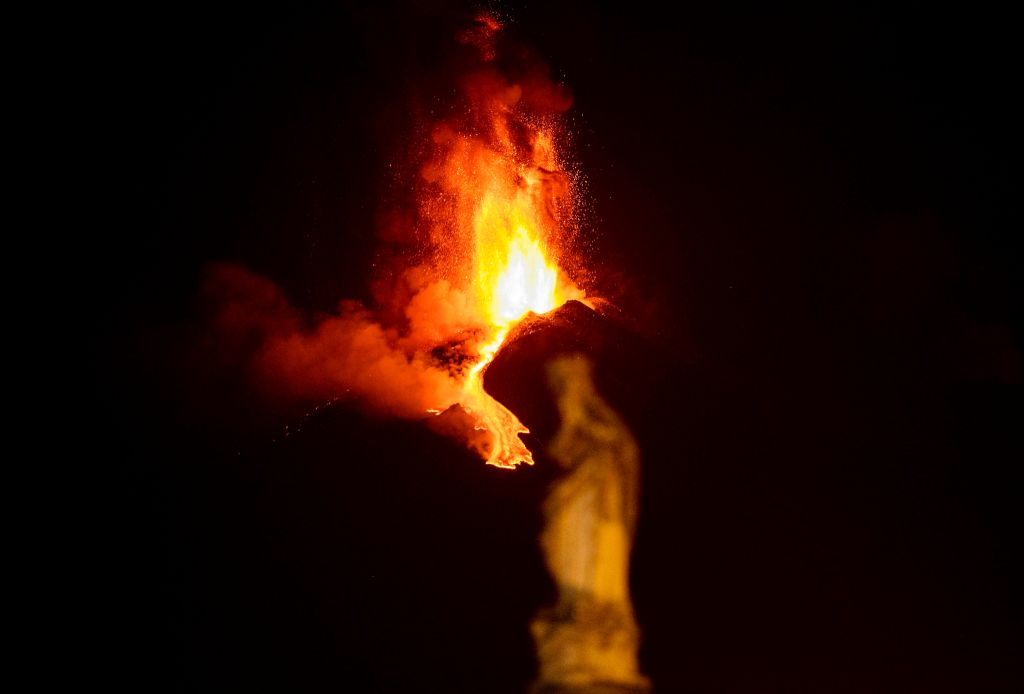 Etna erupting, with a statue out of focus in the foreground