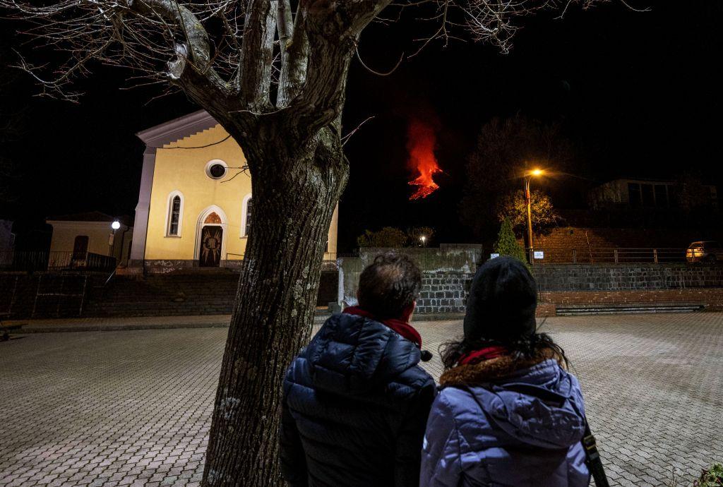 Pedestrians in Zafferana Etnea look toward lava flowing down from Mount Etna