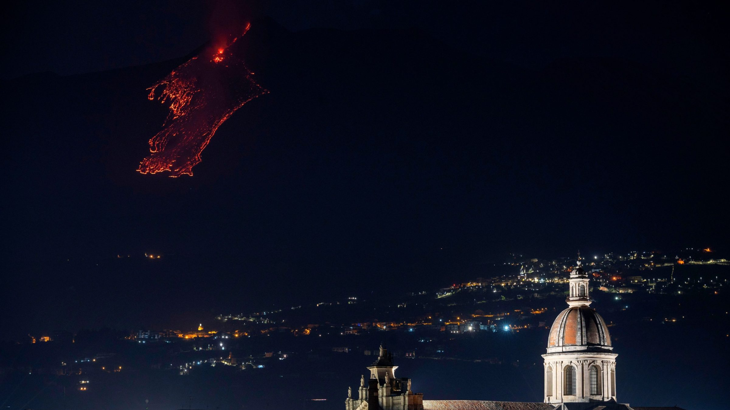 Lava flows down Etna with the city of Catania in the foreground