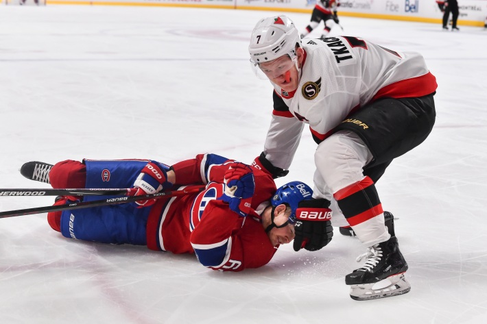 Brady Tkachuk #7 of the Ottawa Senators takes down Artturi Lehkonen #62 of the Montreal Canadiens