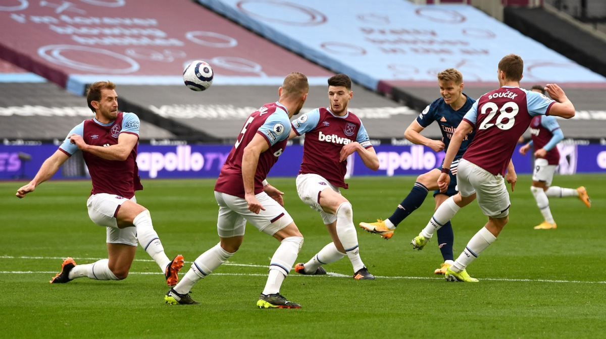 Martin Odegaard of Arsenal has a shot on goal whilst under pressure from Declan Rice and Tomáš Souček of West Ham United during the Premier League match between West Ham United and Arsenal at London Stadium on March 21, 2021 in London, England.