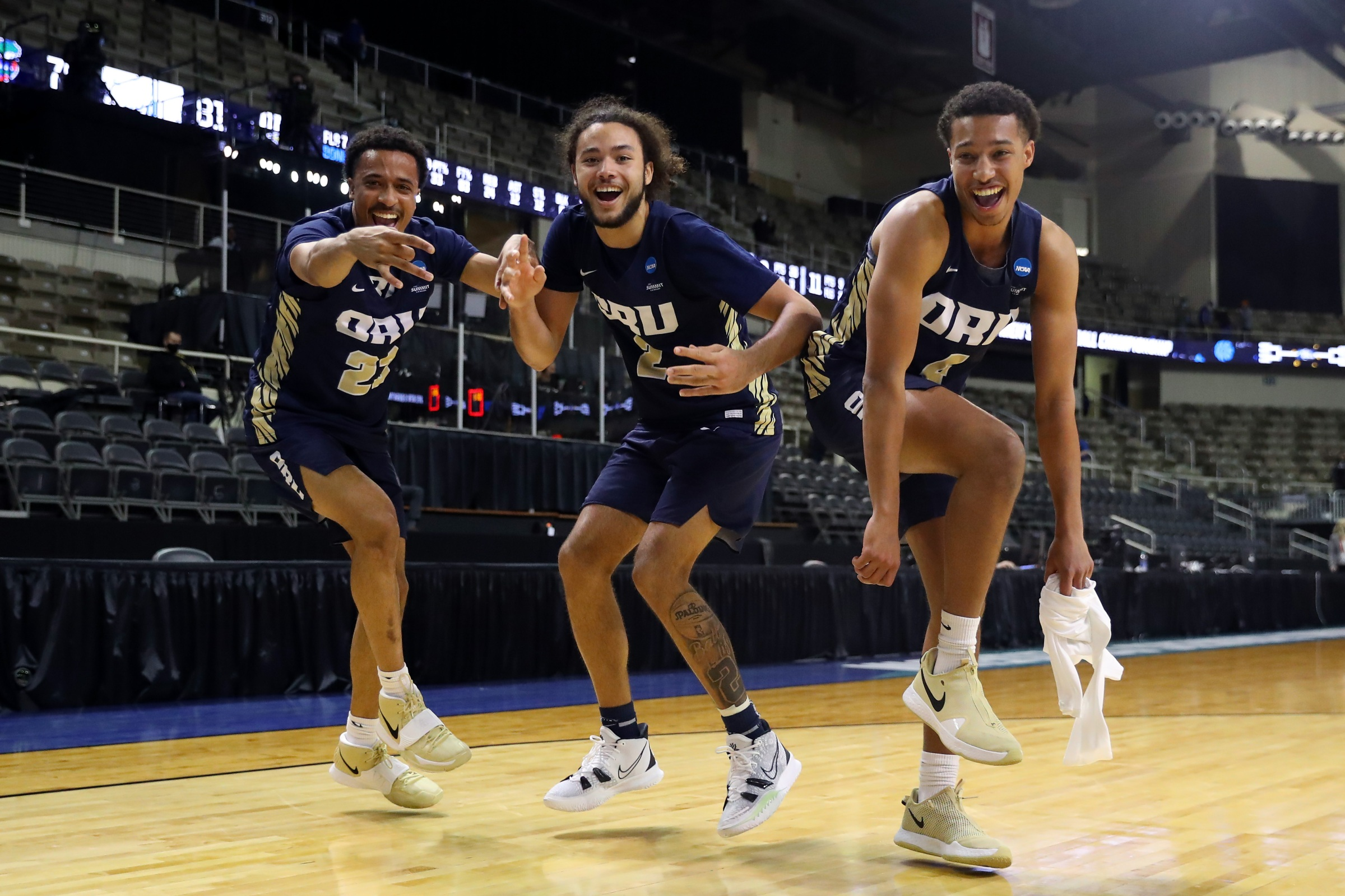 Three Oral Roberts Golden Eagles players dance after their second-round NCAA Tournament win against Florida.